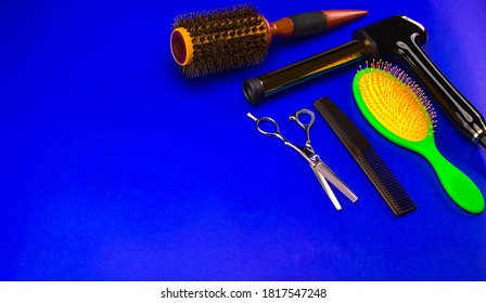 Hairdressing tools, wooden brush, flat brush, comb, scissors, beby liss, clips, on blue background