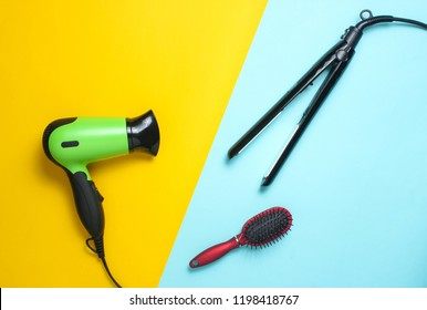 Hairdryer, curling iron, hairbrush on a pastel colored background. Beauty and fashion objects for hair care. Top view