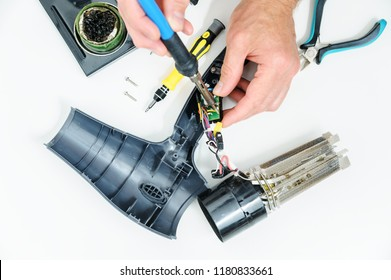 Hairdryer in a disassembled condition on a white background. The man is repairing it.
