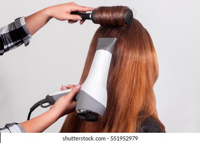 Hairdryer in use. hair styling process by using hairdryer and round brush.