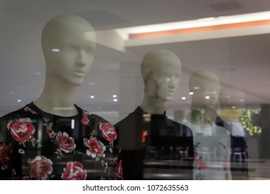 Hairless female mannequins stare through reflections in the window before them