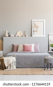Hairpin pouf with book and knit blanket in wicker basket standing on carpet by the king-size bed in real photo of grey room interior with poster and decor