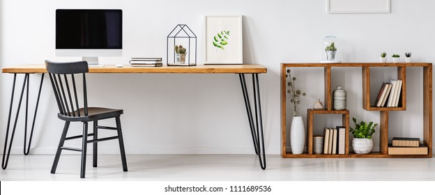 Hairpin table with computer, notebooks, poster and cactus standing in white home office interior with books and plants on wooden shelves