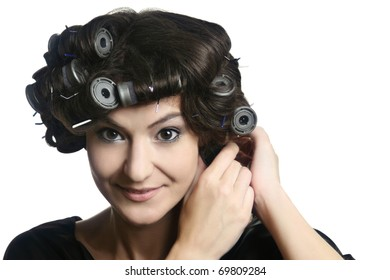 Hair-rollers. Beautiful woman with hair rollers on the head. Hairdo with hair-rollers.