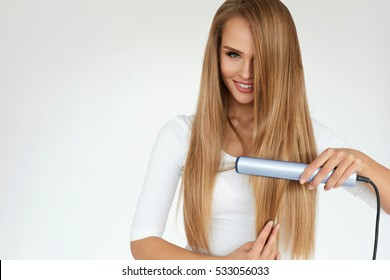 Hairstyle. Beautiful Smiling Woman Ironing Long Blonde Hair With Flat Iron. Portrait Of Girl With Perfect Gorgeous Straight Hair Using Straightener On White Background. Hair Care. High Quality Image