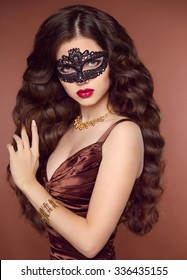 Hairstyle. Beautiful young woman in black mysterious venetian lace mask and coffee brown elegant dress. Fashion jewelry. Luxury accessories.