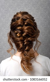 Hairstyle Greek braid on the head of a brown-haired woman back view close-up on a gray background.Fashionable professional women's hairdo.