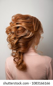 Hairstyle Greek braid on the head of a red hair woman back view close-up on a gray background.Fashionable professional women's hairdo.