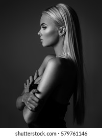 hairstyle, haircare and fashion concept - natural blond woman profile portrait with beautiful hair on grey background in monochrome
