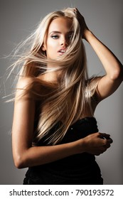 hairstyle, haircare and fashion concept - natural beautiful blond woman portrait with flying hair on grey background