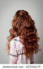 Hairstyle long curls on the red-haired girl turning head to the left on a light background.Professional female hairdress.
