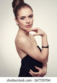 Hairstyle salon model. Pretty Caucasian female with hand adornment posing in studio.