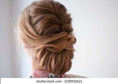 Hairstyle for wedding, loose updo partly made of braid, blonde girl shot from the back on a white background.