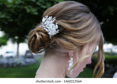 hairstyle of a young beautiful blonde woman with a beautiful white hair clip of beads in her hair styled. Earrings with beads in the ears. Fashionable bride hairstyle for a wedding. Wedding concept.