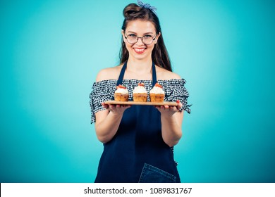 Hairstyled pretty caucasian woman in glasses looking at camera and presenting cupcakes with creamy top on platter
