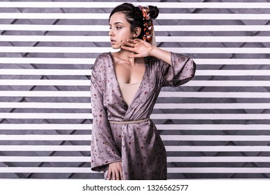 Hairstyles lookbook. Stylish marvelous young mannequin in silk violet maxi gown displaying hairdo with pattern bright kerchief during hairstyles photo session