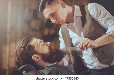 Hairstyling magic. Portrait of a bearded man hipster in a barbershop during haircut