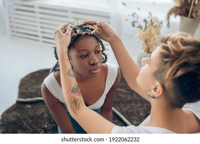 Hairstyling. Short-haired girl doing hairstyling to her girlfriend