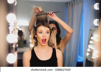 Hairstylist combs client's light-brown with blonde hair. Creating a luxurious evening hairstyle with pain. Dissatisfied customer unhaooy face