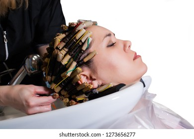 Hairstylist doing a perm placing a heairnet over the tightly rolled curlers in a customers hair before applying the perming lotion