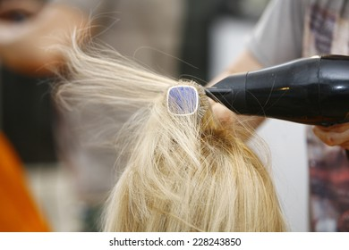 Hairstylist Drying Hair Blonde in Salon for short hair