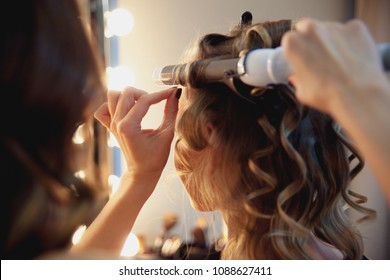 Hairstylist make beautiful curls with curler on light-brown with blonde client's hair. Creating a luxurious evening hairstyle with ringlets of medium length