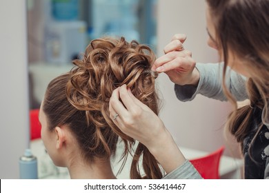 Hairstylist makes the bride with blond hair beautiful high hairdress at the salon