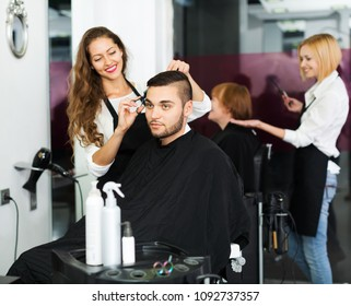 Hairstylist makes the haircut for man in the hairdressing salon
