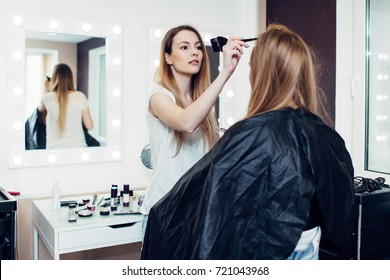 Hairstylist parting the long fair hair of young female customer sitting in cape at hairdressing salon