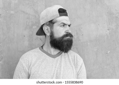 Hairy and bearded. Brutal hipster with thick mustache and beard hair on unshaven face. Hipster on grey wall. Bearded man in trendy hipster style. Caucasian hipster wearing casual baseball cap.