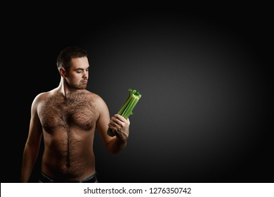 Hairy bearded caucasian man holding a bunch celery isolated on dark grey background. Concept of diet, appetite and potency increasing.