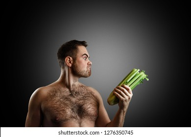 Hairy bearded man watching delightedly to a bunch of fresh celery isolated on dark grey background. Concept of diet, appetite, potency and libido increasing.