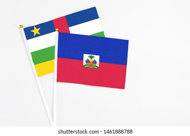 Haiti and Central African Republic stick flags on white background. High quality fabric, miniature national flag. Peaceful global concept.White floor for copy space.