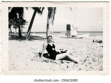 HAITI - CIRCA 1950s: Reproduction of an antique photo shows woman in swimsuit posing on the beach against the backdrop of palm trees and ocean