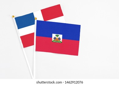 Haiti and Dominican Republic stick flags on white background. High quality fabric, miniature national flag. Peaceful global concept.White floor for copy space.