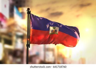 Haiti Flag Against City Blurred Background At Sunrise Backlight 3D Rendering