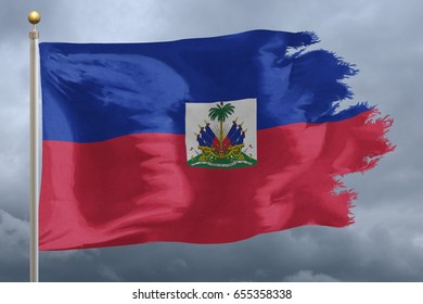 Haiti Flag with torn edges in front of a stormy sky