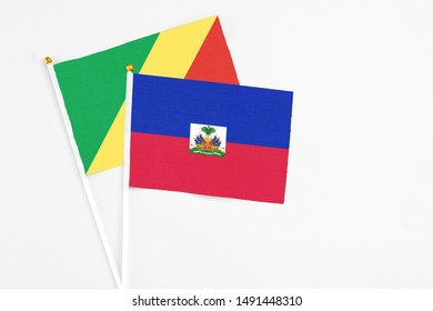 Haiti and Republic Of The Congo stick flags on white background. High quality fabric, miniature national flag. Peaceful global concept.White floor for copy space.