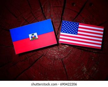 Haitian flag with USA flag on a tree stump isolated