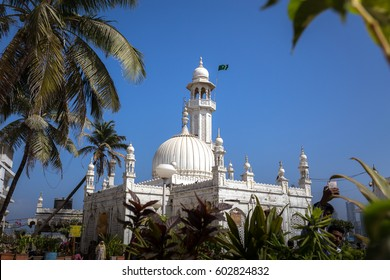 Haji Ali Dargah of Mumbai, surrounded by Palm trees, against blue Sly