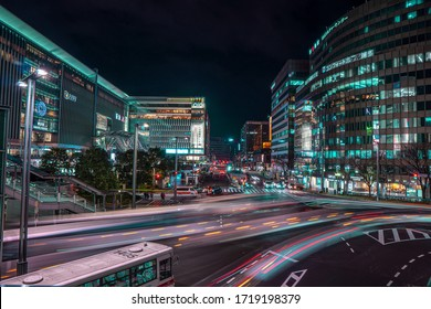 Hakata Station, Fukuoka, Japan - January 17 2020: Cloudy night view of busy traffic on Hakata Station with neon lights and people crossing road. Shot on slow shutter speed.