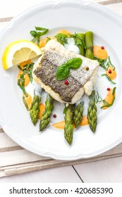 Hake fillet with asparagus foam sauce and lemon, top view