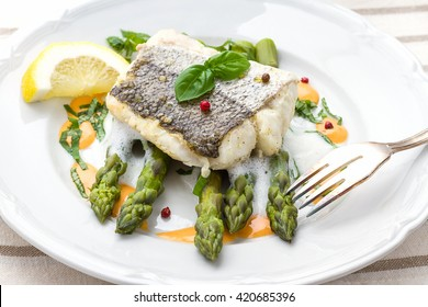 Hake fillet with asparagus foam sauce and fork, top view