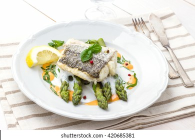 Hake fillet with green asparagus foam sauce and lemon, top view