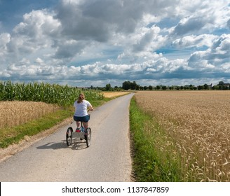 Hakendover, Flanders / Belgium - 07 15 2017: Young woman with Down syndrome driving on a tricycle through the fields at the Belgian countryside