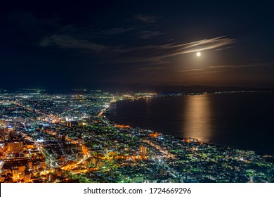Hakodate City night view from Mt. Hakodate observatory, big bright moon light up the sea, golden reflection on surface. Famous scenic spot in the world. Hokkaido, Japan
