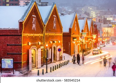 HAKODATE, JAPAN - FEBRUARY 2, 2017: Tourists enjoy a snowy evening at historic Kanemori warehouse district. Hakodate Port was among the first Japanese ports to be opened to international trade.