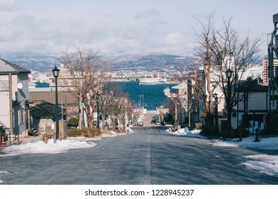HAKODATE, JAPAN - JANUARY 3, 2018 : Hachiman-zaka slope in Hakodate. The famous tourist spot in Hakodate, this popular place for picture-taking, visitors climb a steep hill to mountain & harbor views.