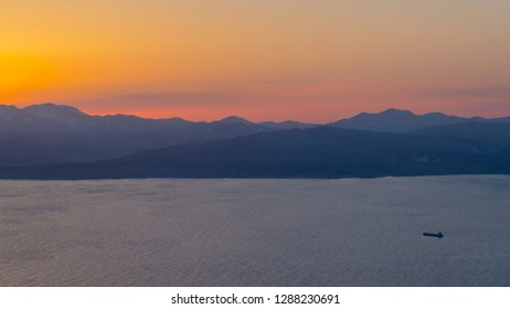 Hakodate, Japan - March 29 2016: A lonely boat sailing in the Hakodate Bay in the light of sunset