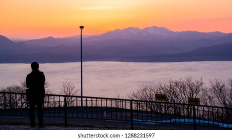 Hakodate, Japan - March 29 2016: A lonely tourist watching Hakodate Bay in the light of sunset